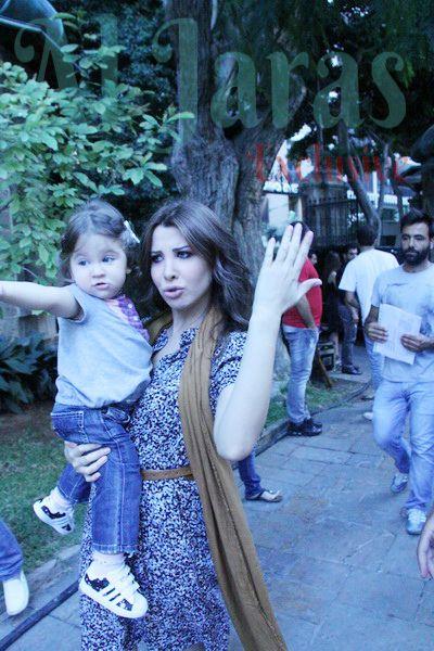 نانسي عجرم تحمل ابنتها في موقع التصوير