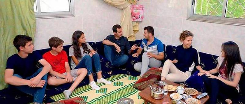 اسماء الأسد مع زوجها رئيس البلاد وولديها في زيارة لبيت سوري فقير