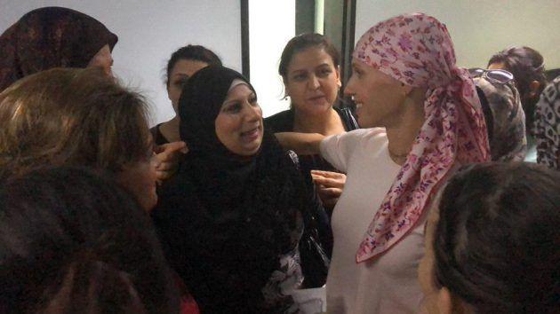 اسماء الأسد تغطي راسها وتستقبل المصابات مثلها