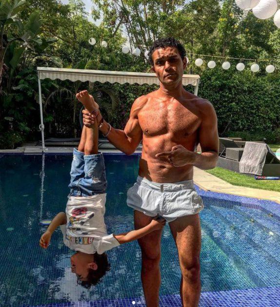 ساخرًا منه،آسر ياسين يمسك بابنه مقلوبا كسمكة محمد صلاح